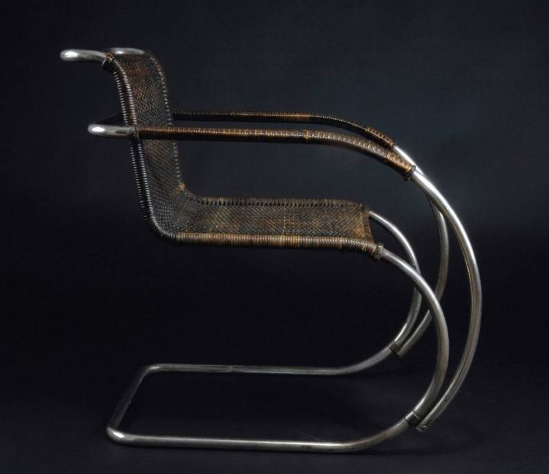 A characterful chair model made from sculpted steel wire – with soft,  removable cushions