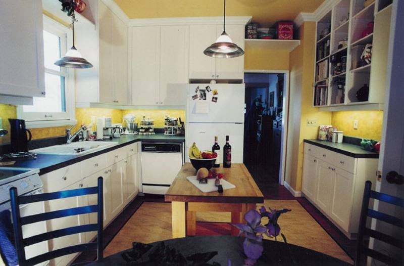 white wooden kitchen cabinet and yellow backsplash connected by white wall and white window