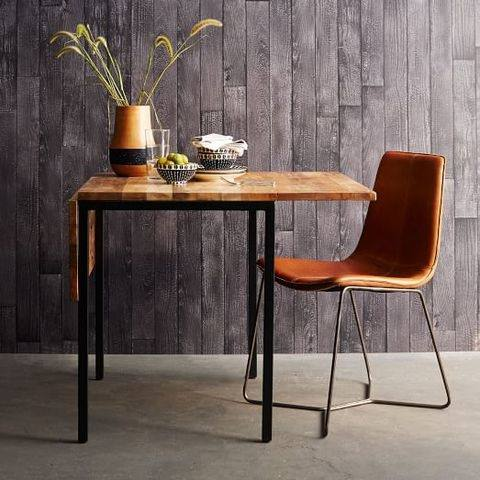 table against the wall, two chairs, one bench seat