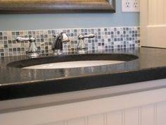 A slightly curved kitchen with a bold glass mosaic tile backsplash and  light granite countertops