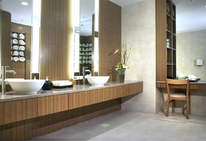 The bathroom showcases a stylish shower room and a sink with smooth  countertop