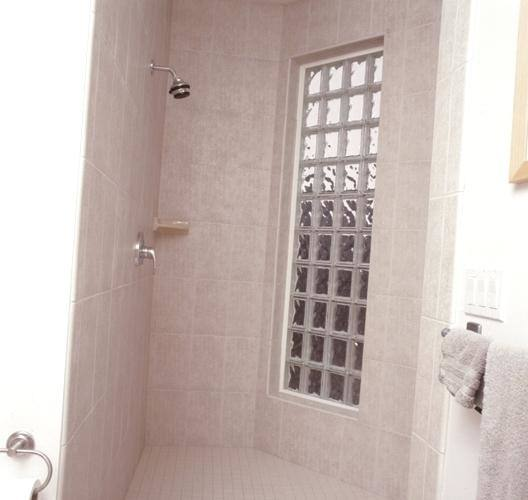 White subway tile, gray grout, glass block window