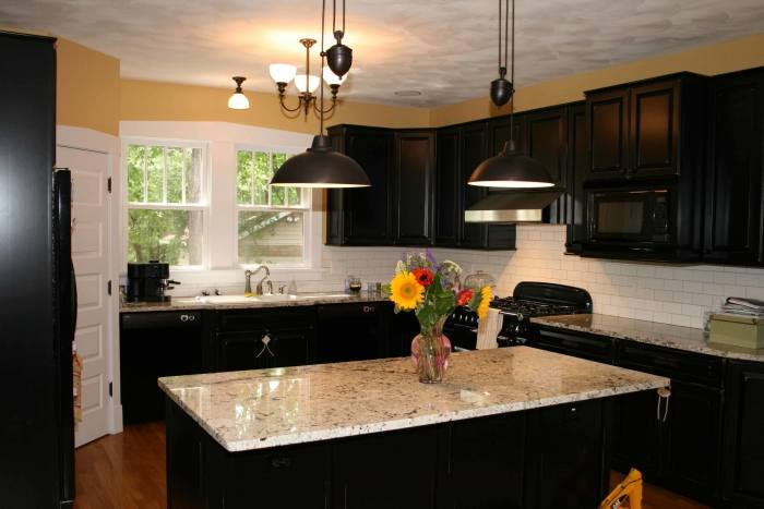 The backsplash, stove hood, gas stove, white cabinets